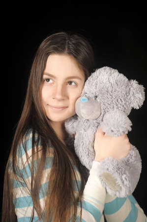 Beautiful young brunette girl with teddy bear.