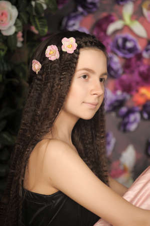 Long-haired brunette girl with flowers in her hair.