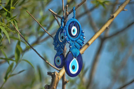 Evil eye charms hang from a bare tree in Cappadocia, Turkey