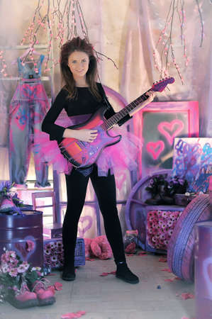 chatoyant: Beautiful young girl in a lilac dress with electric guitar. Stock Photo