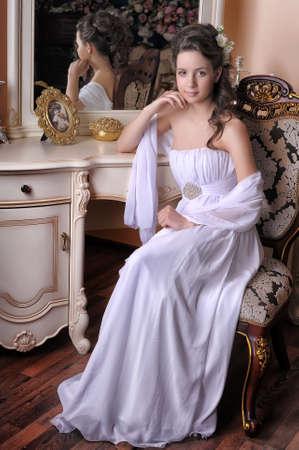 vestidos antiguos: Chica elegante exquisito vestido de blanco sentado en una silla cerca del espejo.