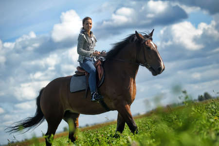 girl in jeans suit on a horse Stock Photo