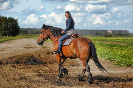 girl in jeans suit on a horse photo