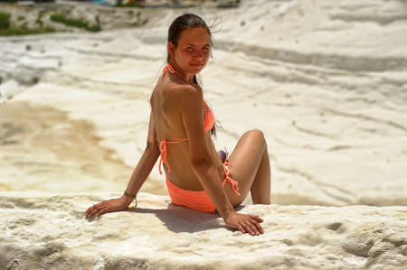 enjoymant: Teen girl in a pink bathing suit on a background in Pammukale calcareous travertine terraces