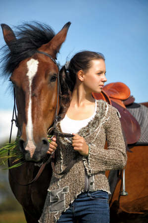 Beautiful young teen girl with the brown horse. photo