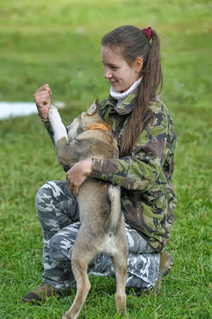 Teen girl playing with a puppy on the grass. photo