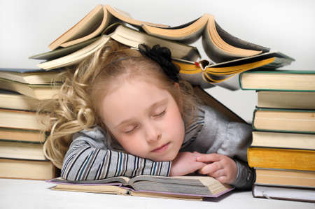 tired Schoolgirl with lot of books photo