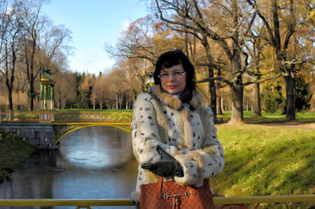 Woman in autumn park on the bridge. photo