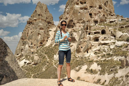 Girl on the background ancient cavetown near Goreme, Cappadocia, Turkey. photo