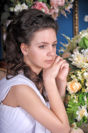Exquisite elegant girl in white dress among the flowers. photo