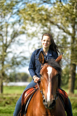 Girl in jeans suit on a horse. photo