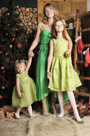 Mother with two daughters in a green dress at Christmas. photo