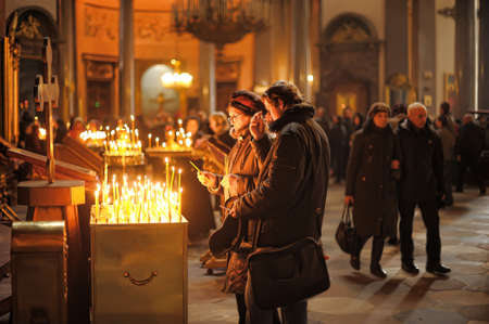 People in the church and light candles, Kazan Cathedral, St. Petersburg, Russia
