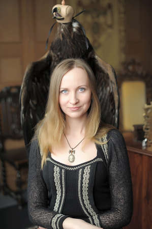 Young woman sitting on a chair with an eagle behind. photo