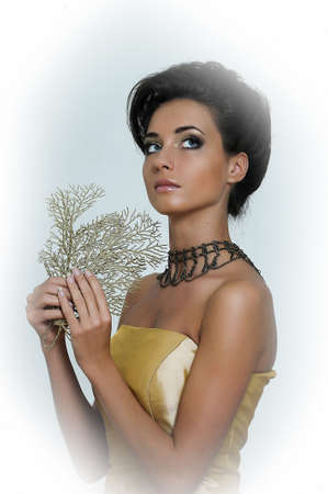 high priced: Beautiful brunette in a golden retro dress Stock Photo