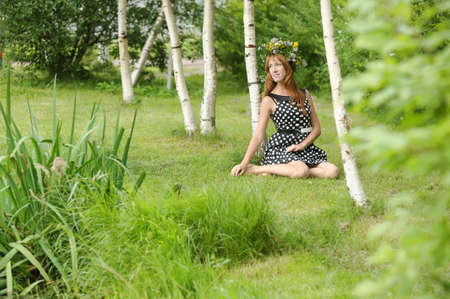 woman wearing a wreath of wildflowers sitting next to a birch photo
