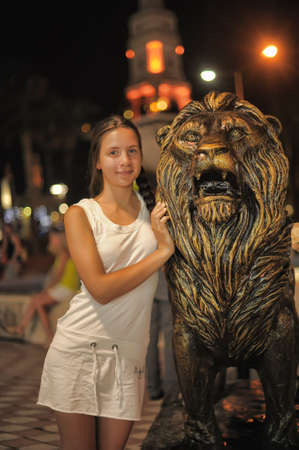 Teen girl in white dress next to the sculpture of a lion, Kemer, Turkey. photo