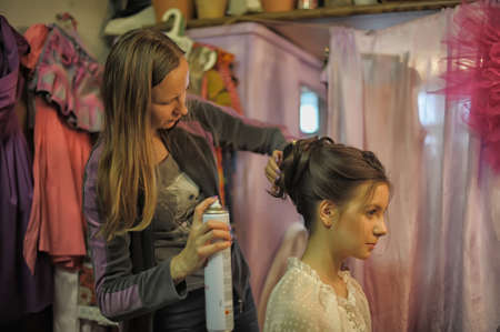 Stylist makes hair model in the dressing room. photo