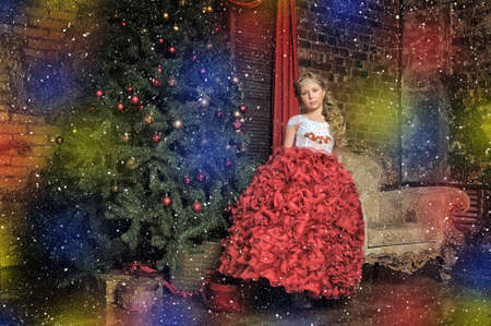 Girl in a smart red white dress at the Christmas tree. photo