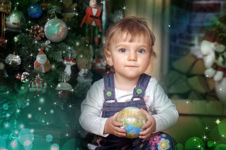Baby girl under the tree with the ball in hands photo