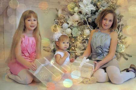 Three girls sisters sitting at the Christmas tree with gifts. photo