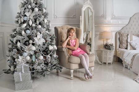 vestido de noche: Chica en un vestido rosa pálido sentado en una silla en el árbol de Navidad en una habitación con un interior blanco.