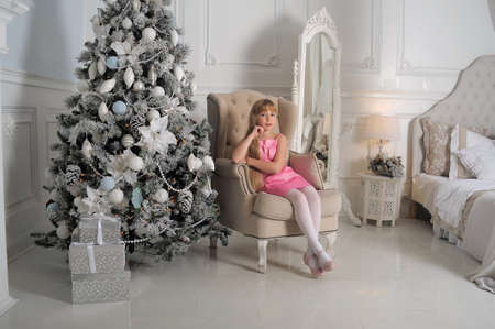 sitting pretty: Girl in a pale pink dress sitting in a chair at the Christmas tree in a room with white interior.
