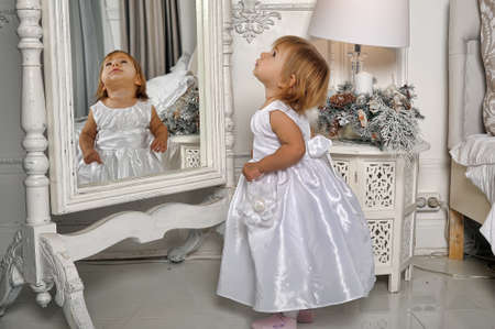 Little girl dressed admires her reflection in mirror photo