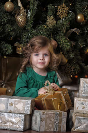 girl under the Christmas tree among the gifts photo
