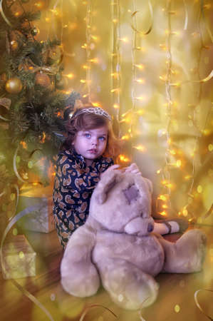 Girl child with teddy bear under the Christmas tree photo