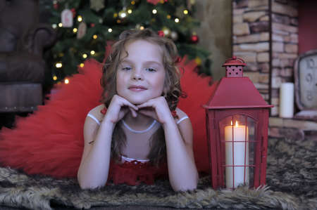 girl in a red dress with a Christmas candle photo