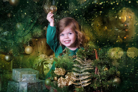 The girl with a gift under the Christmas tree photo