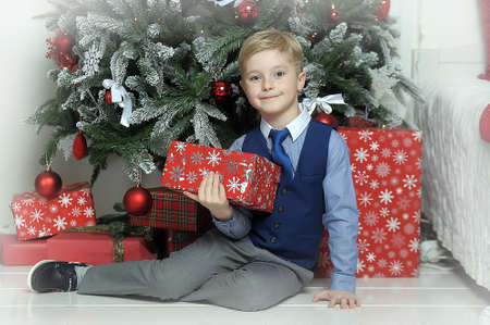 carpet clean: Happy blonde boy with a gift in hands under the Christmas tree Stock Photo