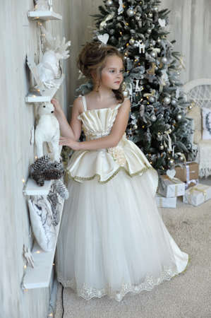 Winter princess in white dress at the Christmas tree. photo