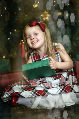 happy girl child holding a gift in the hands of a Christmas photo