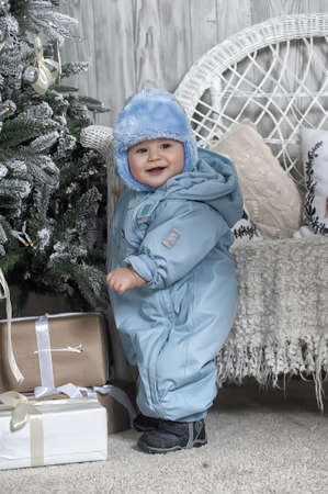 baby open present: Small child in a blue overalls and a warm hat is sitting near the Christmas tree on Christmas.