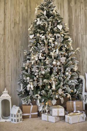Hermosa holdiay habitación decorada con el árbol de Navidad con regalos debajo de ella. Foto de archivo