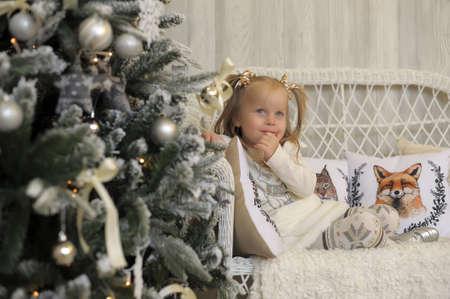 Petite fille dans une robe blanche à Noël.