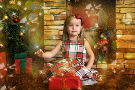 Laughing little girl holding a Christmas gift photo
