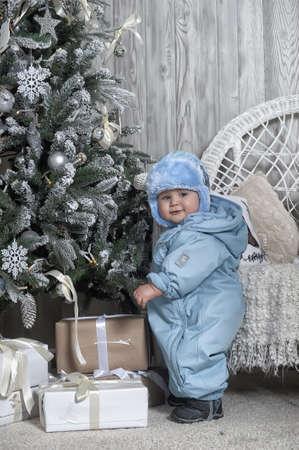 overol: beb� con un mono azul y sombrero de invierno Foto de archivo