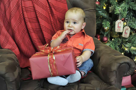 kid with a great gift for a chair at the Christmas tree photo