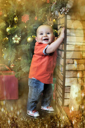 little boy at the Christmas tree with gifts photo