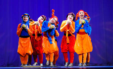 Little children dancing with old oriental costumes on stage