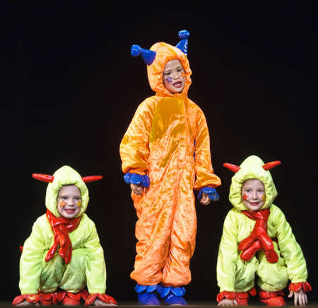 Children in funny colored overalls aliens dancing on stage 版權商用圖片 - 89897806