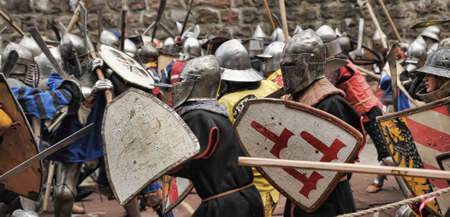 crusaders: Fight between the pedestrian knights in a heavy armor in a medieval castle against a stone wall, Festival of historical reconstruction, Vyborg, Russia.