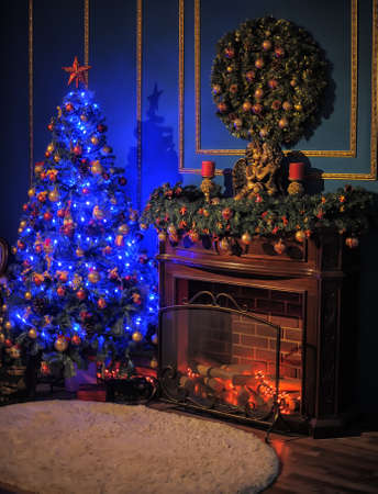 glowing Christmas tree by the fireplace photo