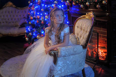 girl in white dress in the fireplace on  background glowing Christmas tree photo