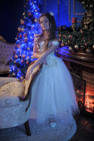 girl in white dress in the fireplace on  background glowing Christmas tree Stock Photo