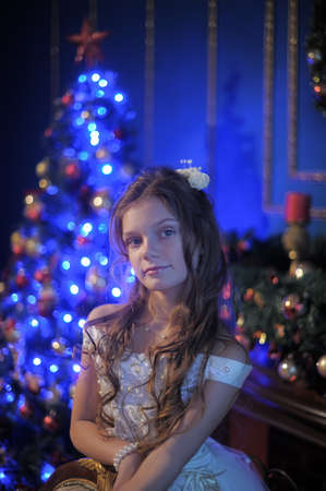 hearthside: girl in white dress in the fireplace on  background glowing Christmas tree Stock Photo