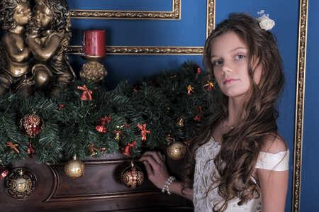 baby near christmas tree: Girl in white dress near Christmas tree. Stock Photo